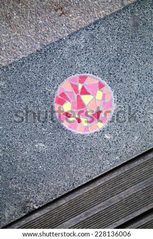round mosiac on the footpath - stock photo