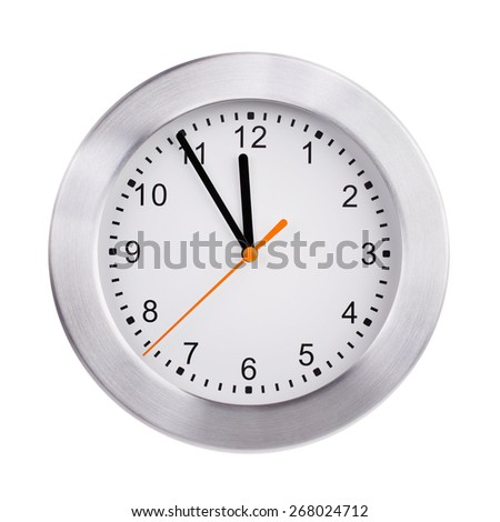 Round office clock shows five minutes to twelve - stock photo