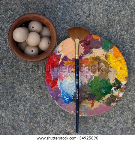round palette with oil and brush and wooden beads in vase on a stone background