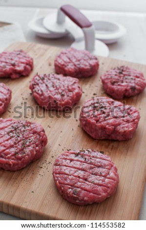 Round patties from ground beef before cooking vertical - stock photo