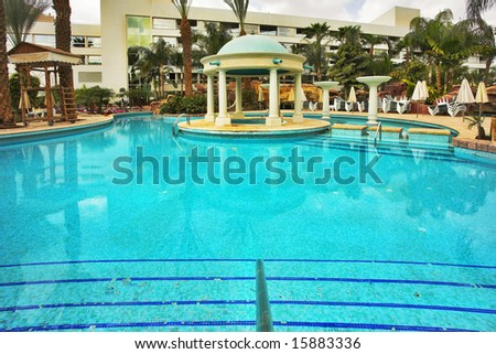 Round pavilion constructed in decorative pool with transparent water in a court yard of dear hotel - stock photo