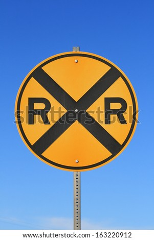 round railroad crossing road sign with blue sky background - stock photo