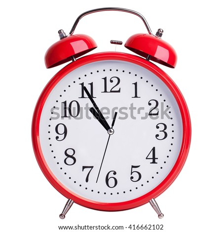 Round red alarm clock is showing almost eleven - stock photo