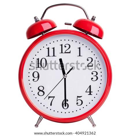 Round red alarm clock shows half past eleven - stock photo