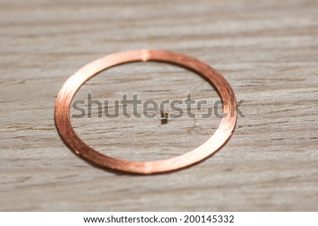 round RFID antenna coil on wooden background - stock photo