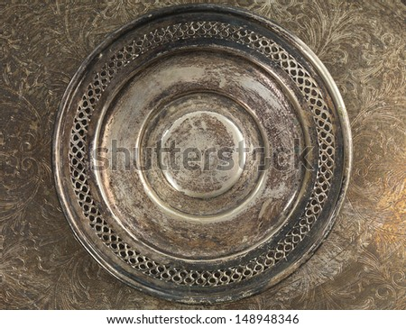 Round rustic silverware plate on metal background - stock photo