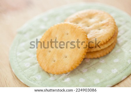 Round salty crackers on white dot green fabric  background - stock photo