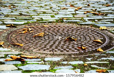 Round sewer manhole on cubical stone road with autumnal leaves . - stock photo
