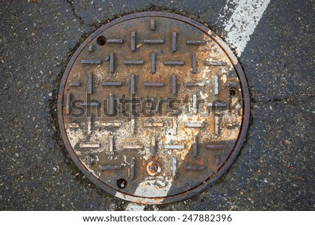 round sewer with a rust and a white line of the road - stock photo