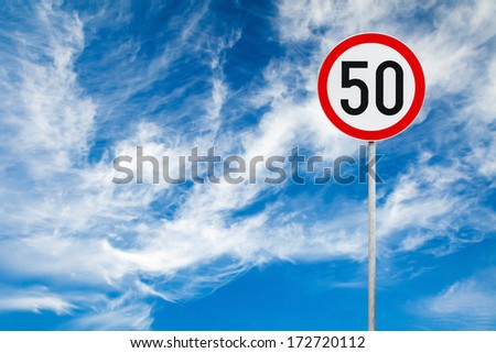 Round speed limit road sign above blue cloudy sky - stock photo