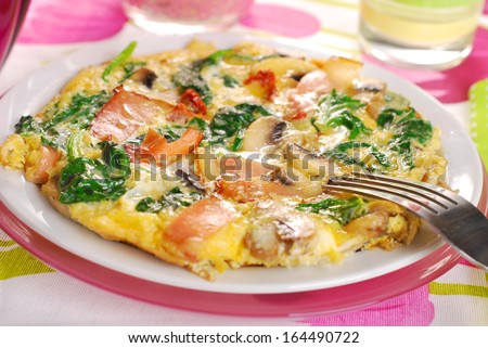 round spinach frittata with mushroom,ham or bacon and dried tomato - stock photo