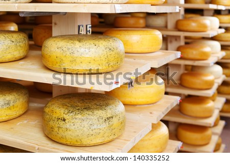 Round stacks of cheese stored on shelves in factory warehouse - stock photo