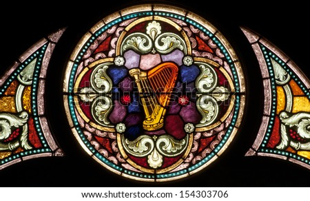 Round stained glass window depicting a harp, symbol of the Psalms - stock photo