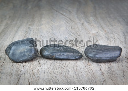 Round stones on wooden texture for a spa. - stock photo