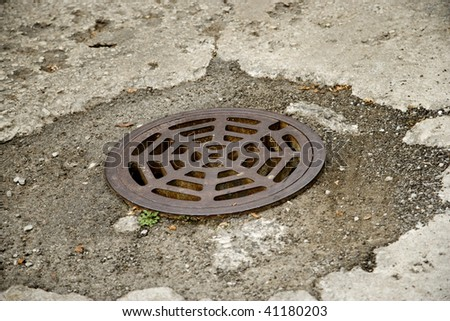 Round Storm Drain in the Road - stock photo