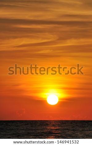 Round sunset and orange sky - stock photo
