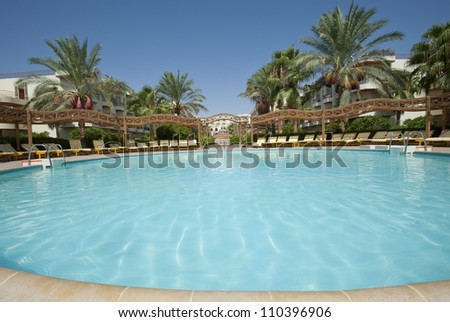 Round swimming pool in a tropical hotel resort with palm trees