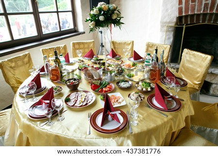 Round table covered with golden cloth served for a frestive dinner