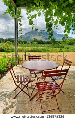 Round table in vine-covered outdoor cafe in mountains. Shot near Stellenbosch and Cape Town, South Africa.  - stock photo