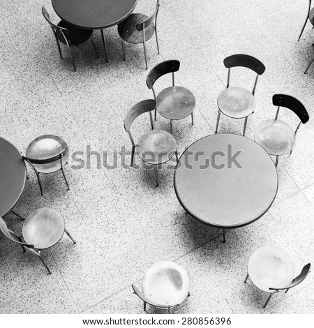 Round tables and chairs stand in empty cafe interior, top view monochrome square photo - stock photo