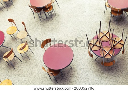 Round tables and chairs stand in empty cafe interior, top view, vintage toned photo - stock photo