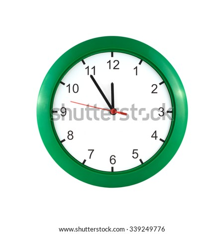 Round wall clock  in green case shows almost twelve hours isolated on white close up - stock photo