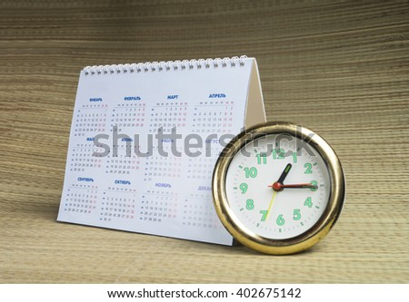 Round watch with desk paper calendar on beige background - stock photo