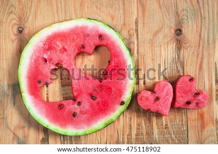 Round watermelon slice with cut in the shape of heart on old wooden background, top view