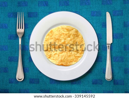 round white plate with slapjack, knife and fork on table  - stock photo