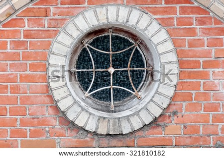 round window with grille on the brick wall closeup - stock photo
