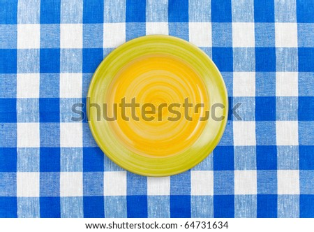 Round yellow plate on checked tablecloth - stock photo