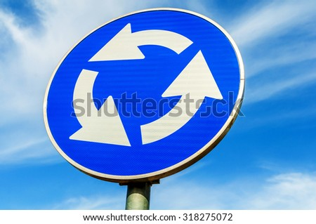 Roundabout crossroad road traffic sign against blue sky - stock photo