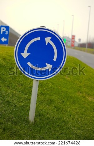 Roundabout traffic sign over grass - stock photo