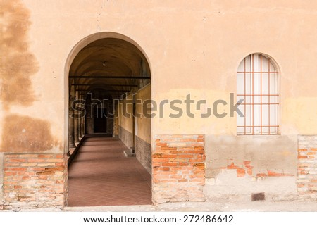 Rounded  stone cloister and window with grate of red iron bars on white wood framed glass. Ancient dark yellow wall of the XV century roman gothic church dedicated to Saint Francis  in Italy