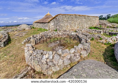 Roundhouse ruins and the reconstructed family nucleus building in Citania de Sanfins. A Castro Village (fortified Celtic-Iberian pre-historic settlement) in Pacos de Ferreira, Portugal. - stock photo