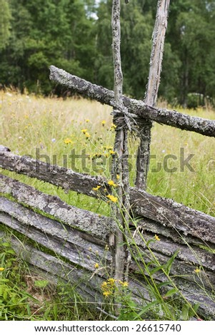 Roundpole fence on a summer meadow