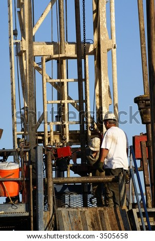 Roustabouts work on lower platform of oil drilling rig, Kern County, California - stock photo