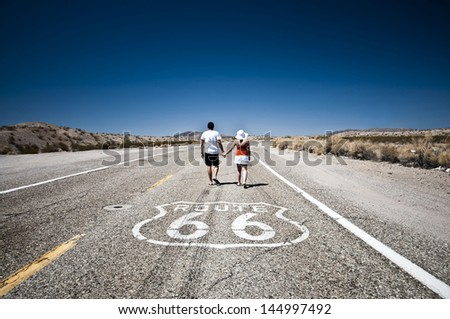 Route 66 -  Couple of tourists walking on the famous highway - stock photo