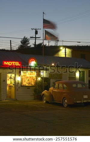 Route 66 neon sign and historic vintage roadside motel welcomes old cars and guests in Barstow California - stock photo