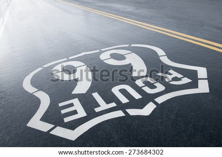Route 66 painted road sign wet after a seasonal rain - stock photo