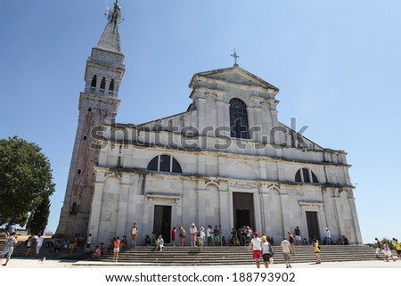 ROVINJ, CROATIA - AUGUST 8, 2012: Tourists strolling around St. Euphemia's Basilica, 18th century Baroque church in the historic center of Rovinj, popular touristic destination in Croatia. - stock photo