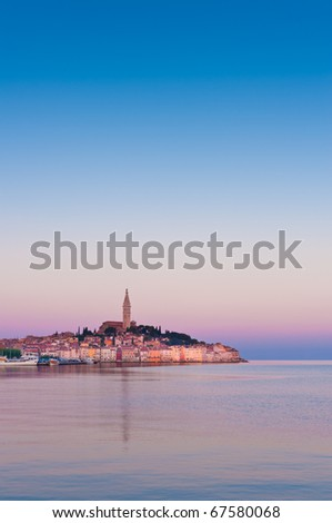 Rovinj old town at Adriatic coast of Croatia, in sunrise light. Istria region, popular touristic destination. Vertical framing with copy-space on sky. - stock photo