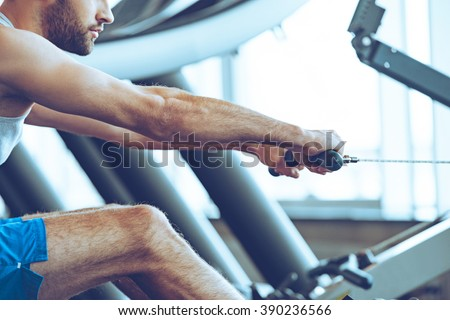 Row and pull. Side view close-up part of young man in sportswear doing rowing in front of window at gym - stock photo