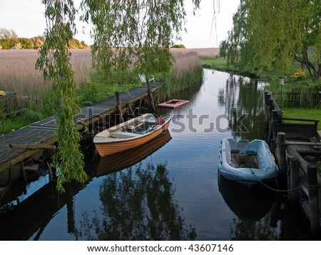 Row boat anchored and reflected in the water of a beautiful stream
