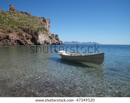 Row boat anchored at shoreline. - stock photo