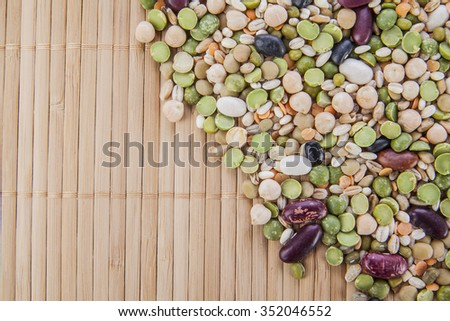 row food background of Groats mix: white and black beans, lentils, peas, pearl barley lie on bamboo table texture  - stock photo