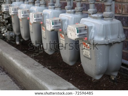 Row gray gas meters at an apartment complex done with a narrow field of focus without manifold - stock photo