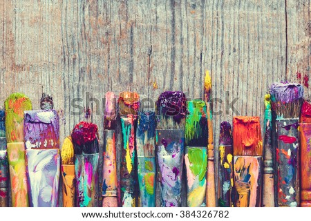 Row of artist paint brushes closeup on old wooden background. - stock photo
