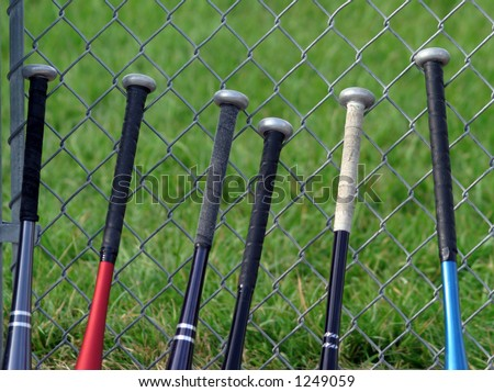 Row of baseball bats lined up against a chain link fence. - stock photo