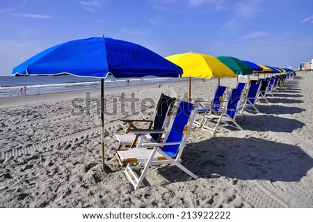 Row of beach chairs and umbrellas - stock photo